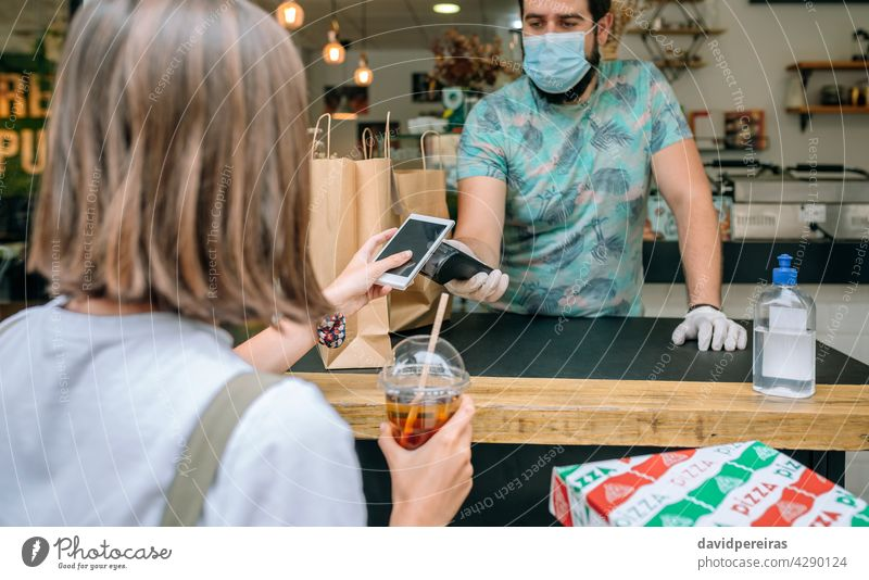 Woman paying with mobile a take away order woman cell phone nfc pos terminal coronavirus food delivery drink protective mask face mask restaurant picking up