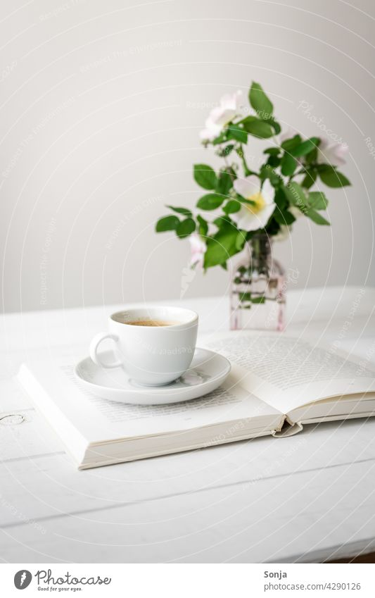 A cup of coffee on an open book and flowers in a vase on a white wooden table Coffee Cup Bay Open Wooden table White Vase Still Life at home Coffee break