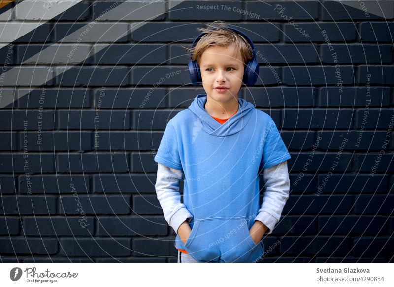 Blonde Caucasian boy in a blue hoodie and headphones stands on a city street against a gray brick wall, listening to music in a good mood lifestyle portrait