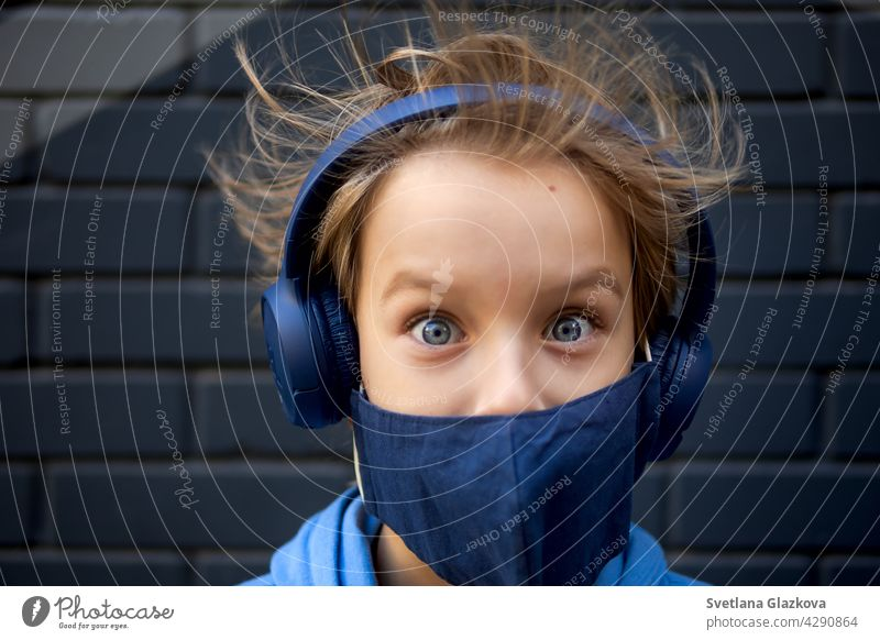 Funny portrait of a blonde caucasian boy whose hair rises and flies in the wind. Looks at the camera.Dressed in a protective medical mask and blue headphones