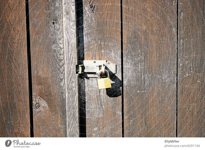 Old wooden wall of a barn with a simple lock. Wooden wall Brown completed Lock Padlock door Barn Wooden door Closed Simple background Metal Metal lock Entrance
