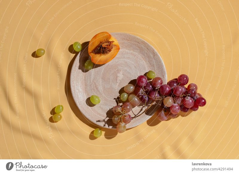 Sliced fresh peach and grape on homemade ceramic plate on yellow tablecloth, fruits catering grapes Fresh Diet Vitamin Summer Snack Peach Food Detox Plate