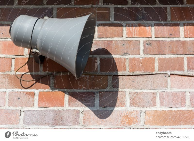 Megaphone in front of an old brick wall advertisement advertising alarm alert announce announcement attention Background beware broadcasting careful caution