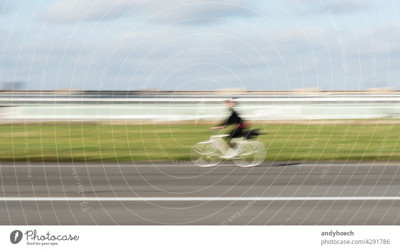 Woman cyclist in motion on a straight asphalt road abstract action active activity adventure Background bicycle bicyclist Bike biker biking blur blurred city