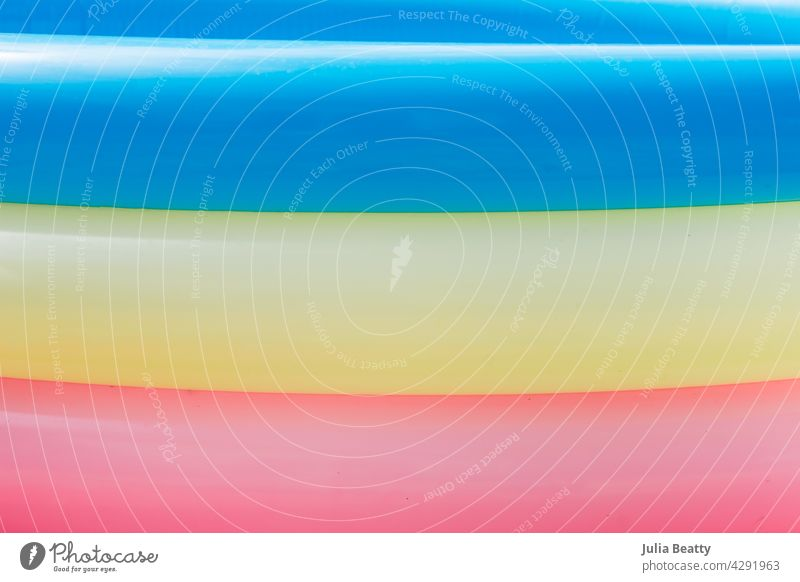 Summer: closeup of the side of blow up pool with blue, yellow, and pink rings summer inflated round puffy traditional candy bright faded abstract pride lgbtq