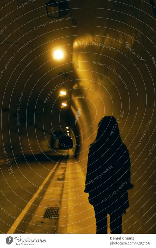 Girl's Back In The Night Tunnel Dark Mysterious lonely Exterior shot Night shot one person road Design darkness Uniqueness Man contrasts Interior shot Light