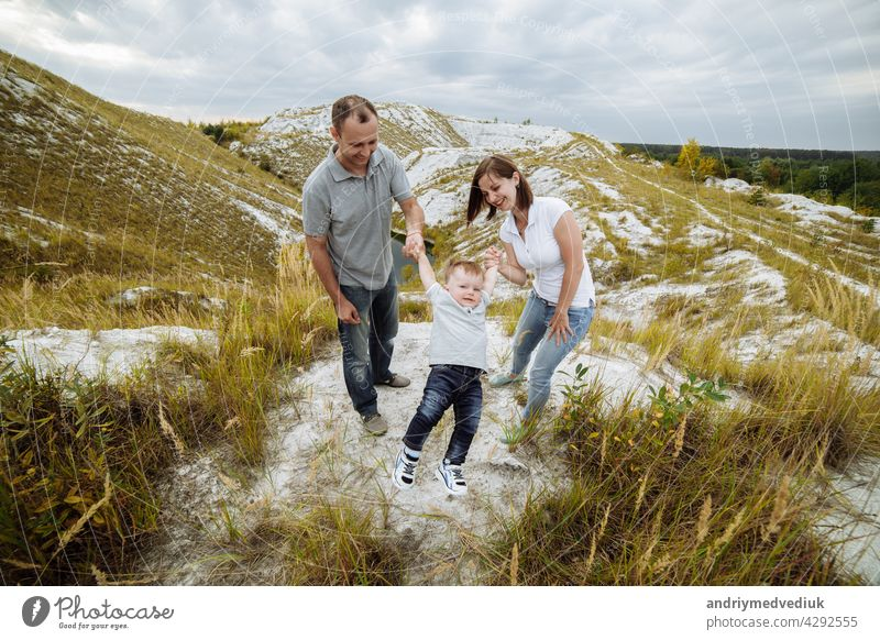 Mom, dad hugging son in the sand mountains enjoy and look at nature. Young family spending time together on vacation, outdoors. The concept of family summer holiday. Mother's, father's, baby's day.