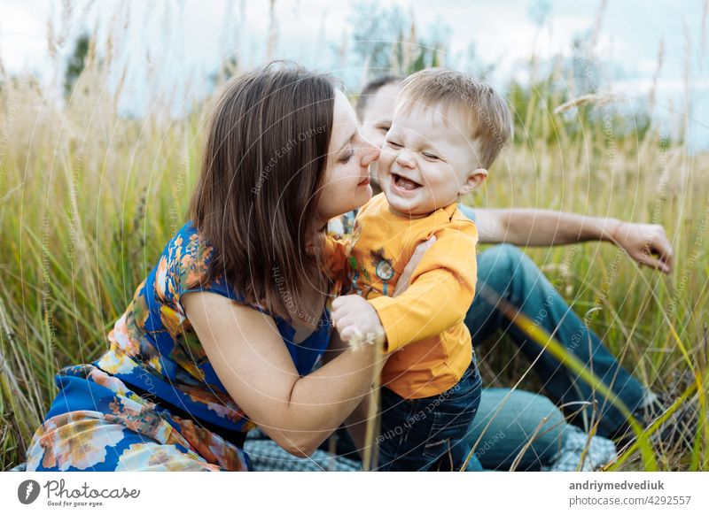happy family having fun outdoors in grass. Family enjoying life together at meadow. Mother, father, little boy smiling while spending free time outdoors mother