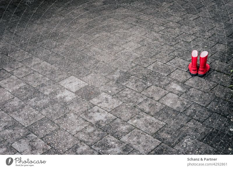 red rubber boots on stone floor Rubber boots Red Paving stone Stone floor Children's shoes Playing feet out sealed Gray Exterior shot Colour photo Deserted
