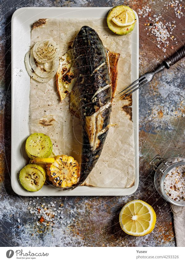 Top view delicious grilled mackerel with vegetables on a rectangular plate. Appetizing roasted sea fish with corn, zucchini and spiced lemon. Mediterranean Kitchen. Healthy seafood. Vertical shot