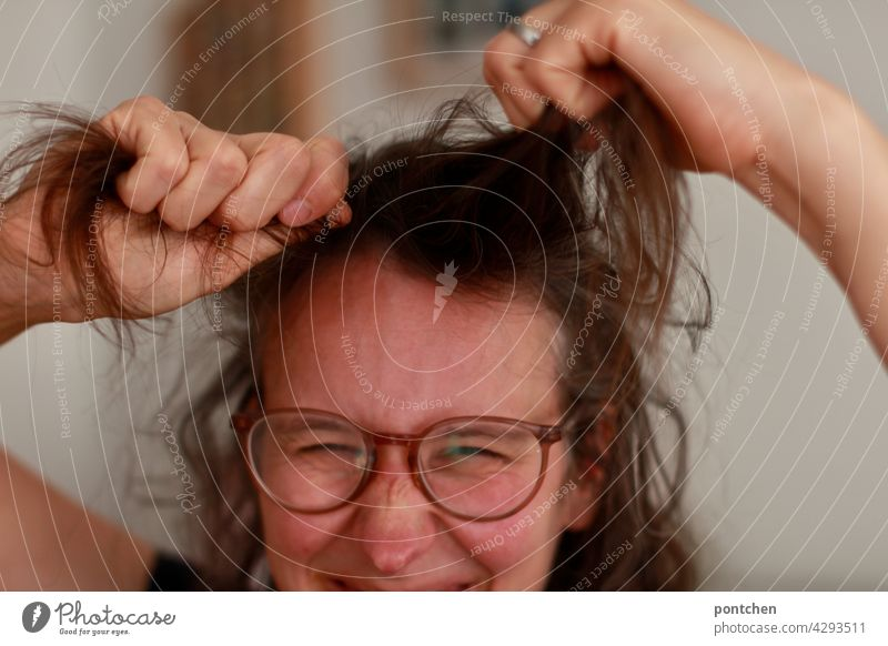 it's hair pulling. proverb. woman gets annoyed. grimaces Aggravation Anger emotion Proverb Woman Pull Brunette Eyeglasses Grimace Hideous Humor Face