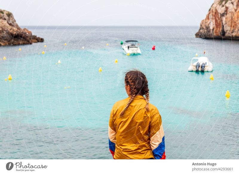 Young blonde woman looking at the boats docked in a small harbor on the island of menorca. young blue holiday vacation water paradise calm mediterranean ocean