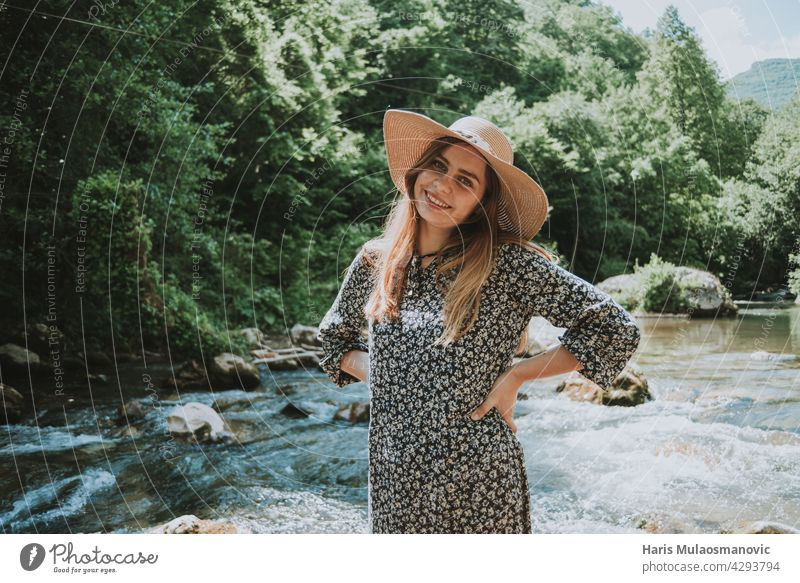 pretty blonde woman with hat by the river in nature accessory adult attractive away from the city beautiful beauty bridge caucasian dress elegant face fashion