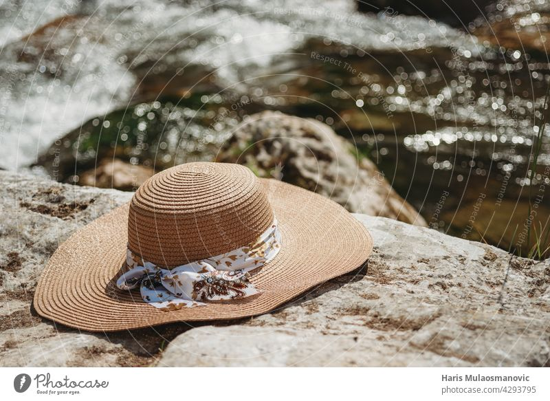 Summer hat on the rocks by the river accessory background beach blue close-up coast concepts couture directly elegance enjoy fashion frame holiday image life