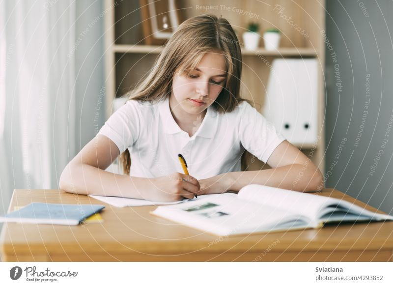 A high school student takes notes from a book, a teenage girl does her homework and prepares for lessons. Education, training, homework write desktop study