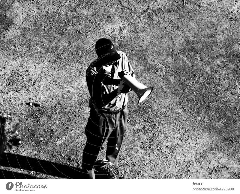 A man with a megaphone body-conscious Places Stand sun cap Shirt Lanky Thin Man Demonstration Megaphone Speech announcement