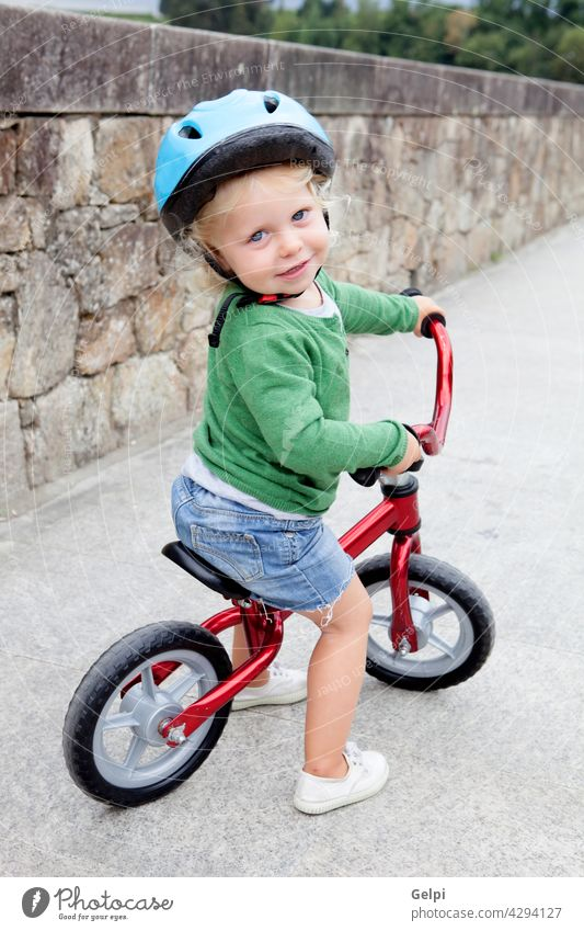 Little kid riding his bike down child bicycle summer baby little park safety happy toddler outside active ride sport helmet young outdoor fun wheels spring