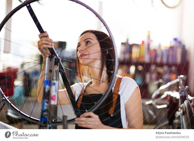 Young woman working in a bicycle workshop Sales Representative Bicycle Bicycle mechanic Cycling bicycle shop Business Retail sector Cycle helpful indoors Woman