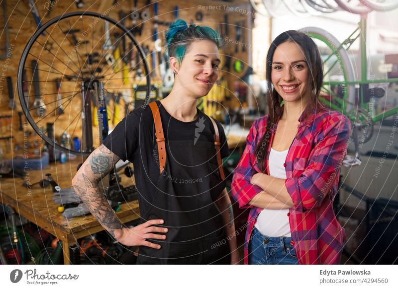 Two young women working in a bicycle repair shop sales clerk bicycle mechanic bicycling bike shop business retail helpful indoors woman female manager owner