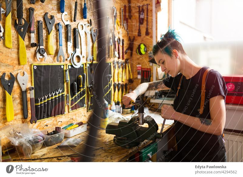 Young woman working in workshop sales clerk bicycle bicycle mechanic bicycling bike shop business retail helpful indoors female manager owner profession repair