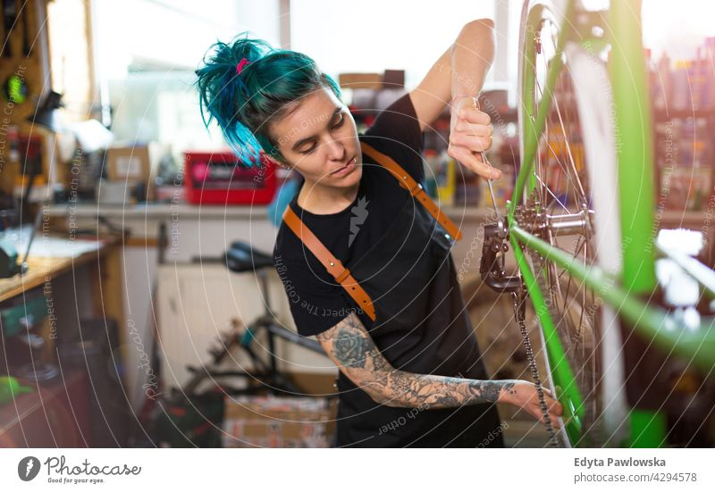 Young woman working in a bicycle repair shop sales clerk bicycle mechanic bicycling bike shop business retail helpful indoors female manager owner profession