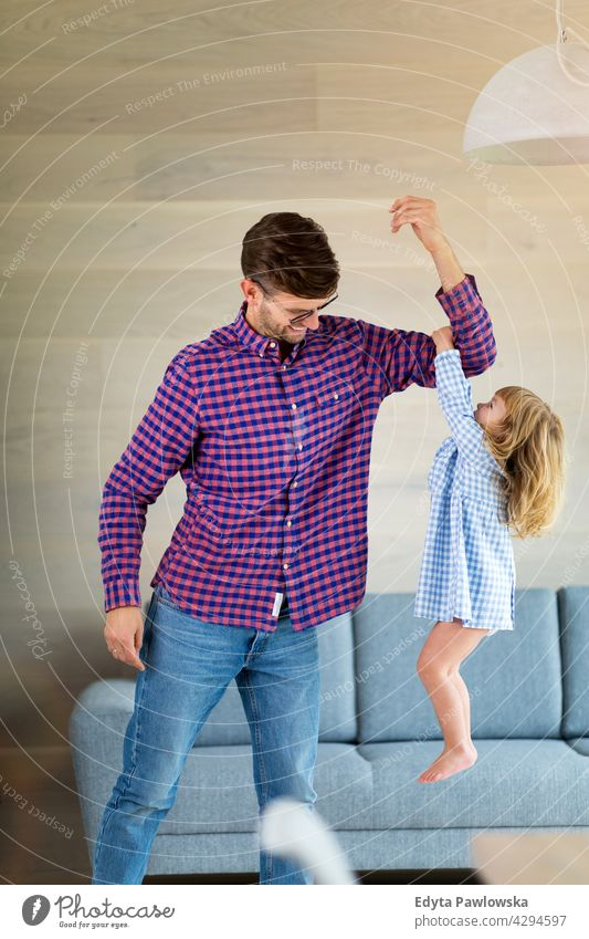Little girl holding on to her father's arm as he lifts her up home house man dad family parent relatives child daughter little girl kid kids children