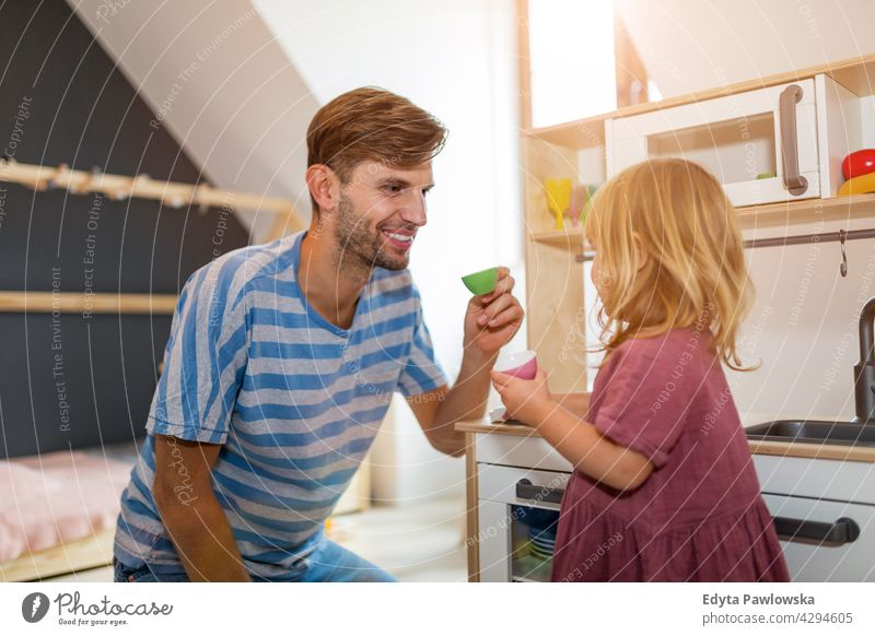 Father and daughter having a tea party at home house man dad father family parent relatives child girl little girl kid kids children relationship together