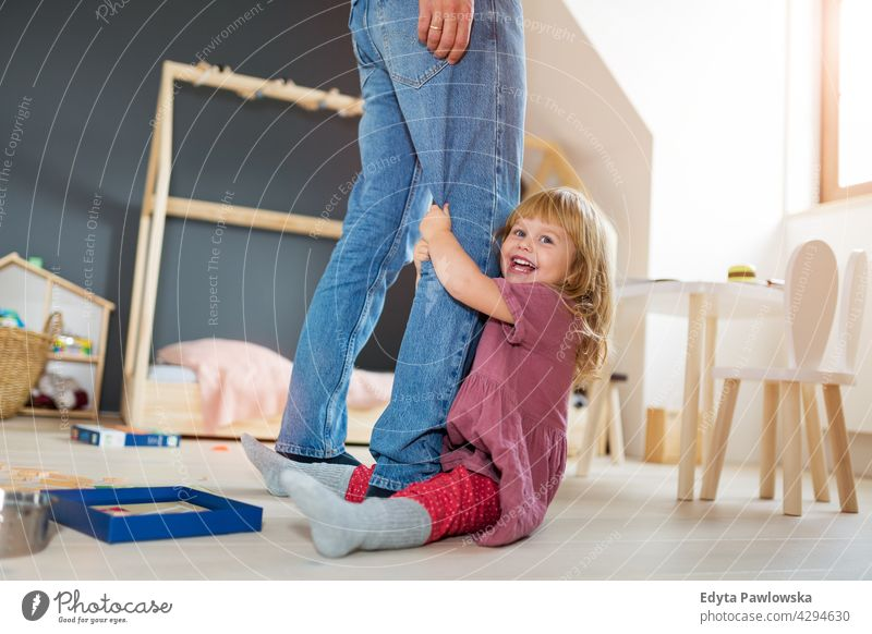 Little girl clutching father's legs home house man dad family parent relatives child daughter little girl kid kids children relationship together togetherness