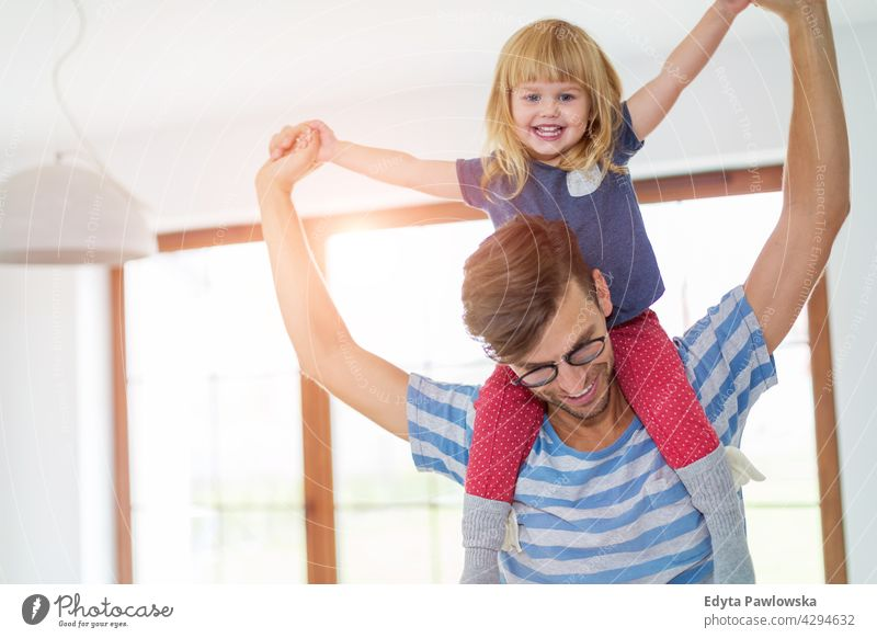 Father Giving Daughter Piggyback Ride home house man dad father family parent relatives child daughter girl little girl kid kids children relationship together