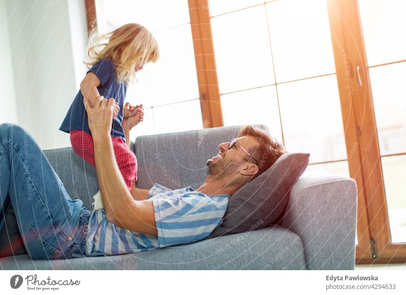 Happy father playing with daughter on sofa at home house man dad family parent relatives child girl little girl kid kids children relationship together