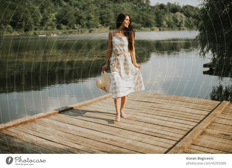 Relaxing young woman standing on wooden pier at the lake beautiful concept enjoy summer nature caucasian good casual female sunny dream person vacation leisure