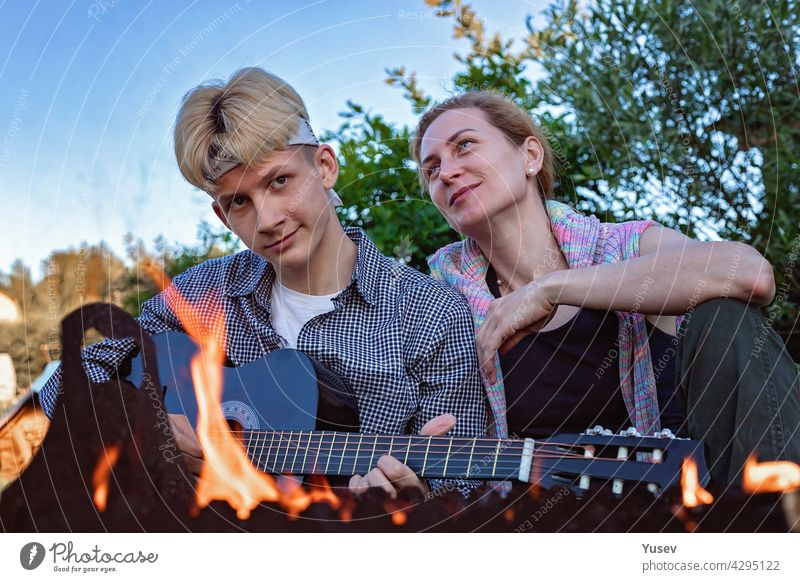 Happy cheerful mom and son sit in the backyard near the fire and play an acoustic guitar. They sing songs and enjoy a summer evening. Summer lifestyle photography. Blue sky background.