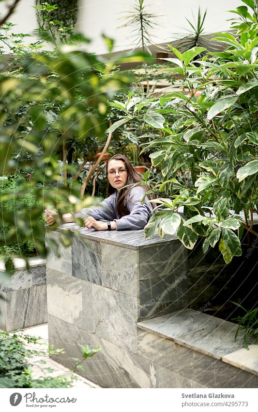 Young brunette girl uses mobile phone texting on smartphones messages makes selfie while sitting in the botanical garden of the city library woman public