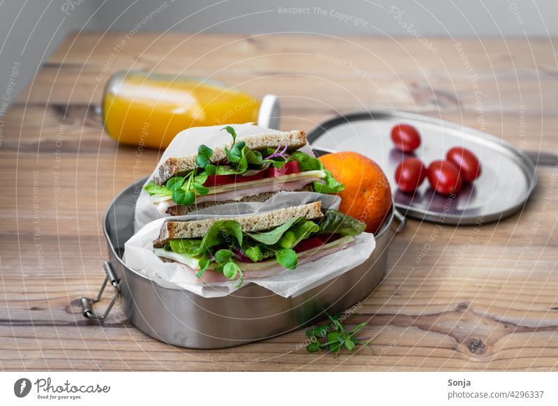 Sandwich in a reusable tin can, cocktail tomatoes and orange juice on a wooden table sandwich Bread for the break Tomato Lettuce Lunch Delicious Reusable