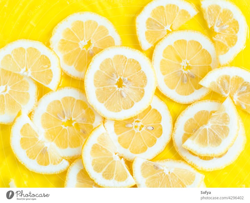 Lemon citrus slices in water with ripples, bold yellow texture summer background lemon fresh fruit food vitamin color pattern cut flatlay flat lay liquid
