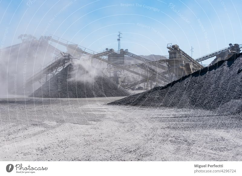 Arid quarry with moving mechanical belt line to separate gravel by size, all wrapped in a cloud of dust. conveyor sand and gravel gravel pit arid construction