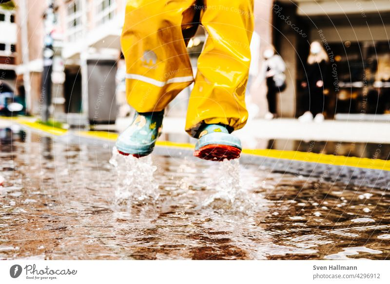 Child jumps happily into a puddle Puddle Water reflection Asphalt Street Wet Reflection Jump Rain Ground Bad weather Weather Clouds Playing feet Freedom Infancy