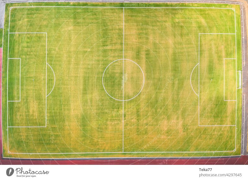 a small football field from above sports football field top down green grass sun lines football field in summer