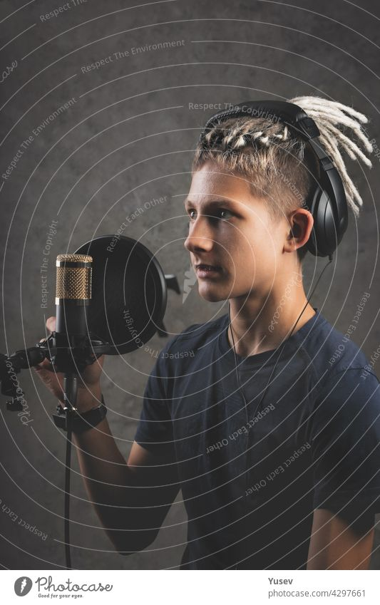 Vertical shot stilysh guy with dreadlocks is recording a song in the studio. A young attractive singer in black studio headphones stands in front of a microphone and sings. Generation Z young talent