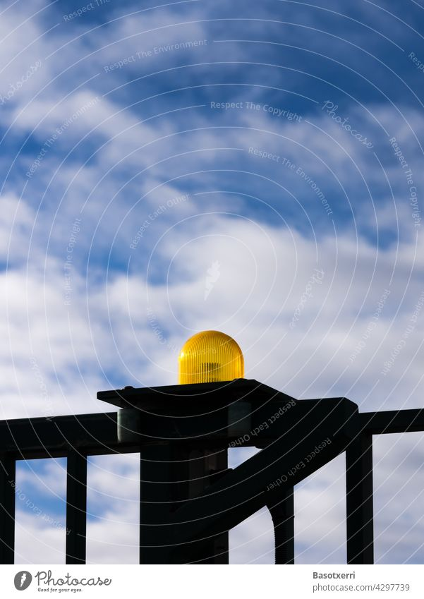 Yellow warning light at an automatic gate, blue sky and white clouds in the background Warning light Flash signal Goal Fence Gate peril Grating Movement Barrier