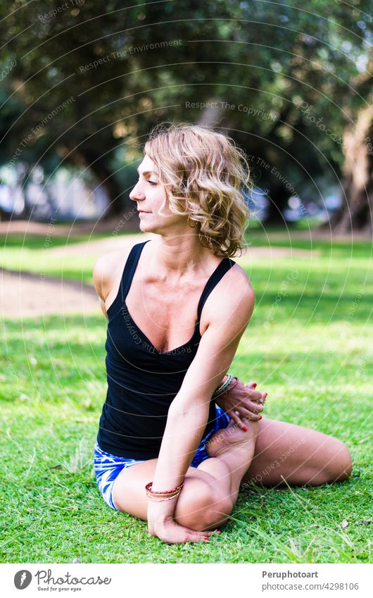 Pretty woman doing yoga exercises in the park. pose balance healthy sport girl people body morning relax lifestyle beautiful care female fitness relaxation slim