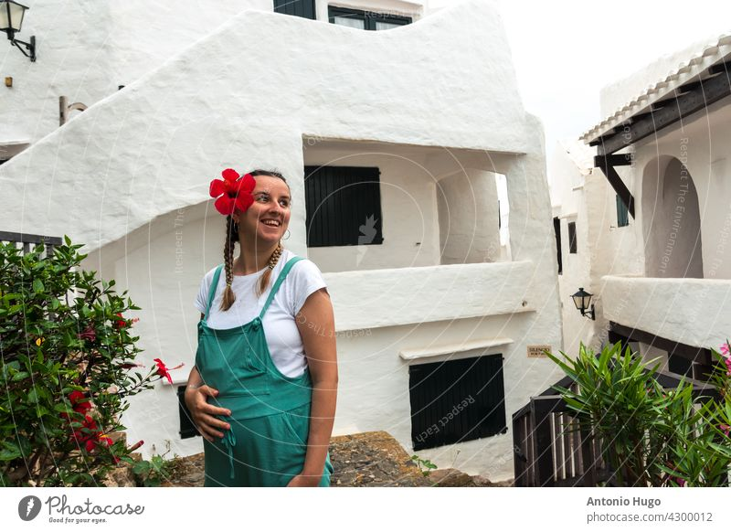 Young pregnant woman with a red flower in her hair walking through a village of white houses on the island of Menorca. young dungarees touching belly tummy