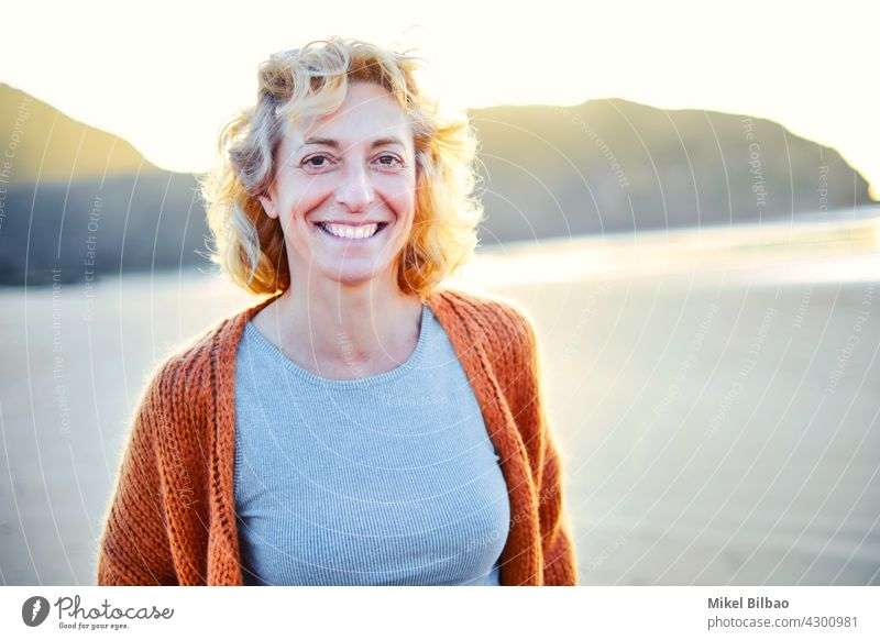 Young mature blonde caucasian woman outdoor in a beach in a sunny day. Lifestyle concept. lifestyle portrait wellness women healthy relaxation lifestyles joyful