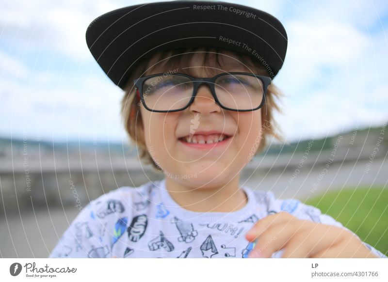 child wearing a hat and glasses smiling at the camera Style Design Human being Emotions Colour photo Child Parents Contrast Neutral Background
