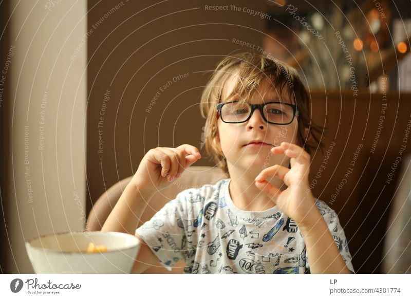 child wearing glasses looking inquisitive at the camera and playing with his fingers Style Design Human being Emotions Colour photo Child Parents Contrast