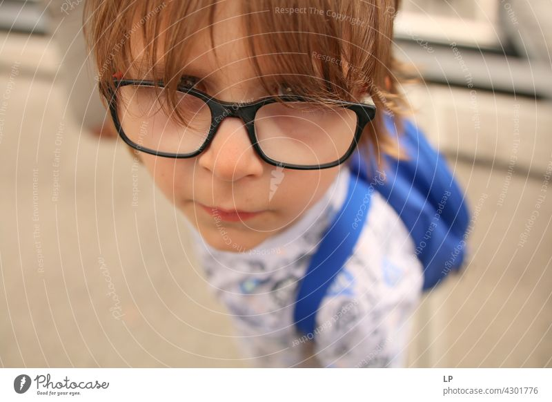 child wearing glasses looking curious at the camera Style Design Human being Emotions Colour photo Child Parents Contrast Neutral Background