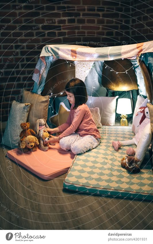 Girl playing with stuffed animals in a teepee lovely girl play mats bed sheets chairs kid childhood female toy joy sweet beautiful little cute people person