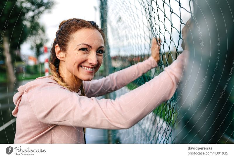 Sportswoman with boxer braids smiling leaning on a metal fence sportswoman looking camera active friendly female girl power happy hood portrait pretty stylish