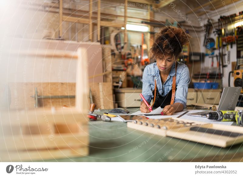 Young craftswoman in her workshop female owner profession service small business employee working technician workplace manual worker maintenance adult people