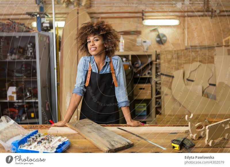 Confident young woman working in workshop female owner profession service small business employee technician workplace manual worker maintenance adult people